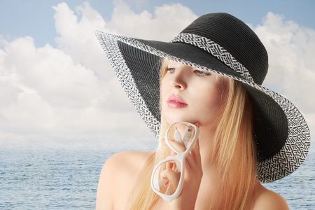 sidewards: Young sexy blonde girl in sun-hat at sea beach looking sidewards Stock Photo