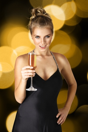 Young sexy woman in black elegant dress holding wineglass with champagne