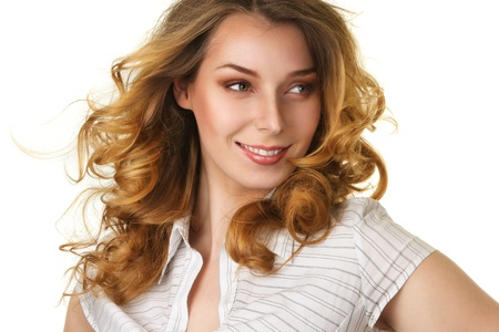 flowing hair: Attractive smiling woman with long curly hair flowing under wind isolated over white background