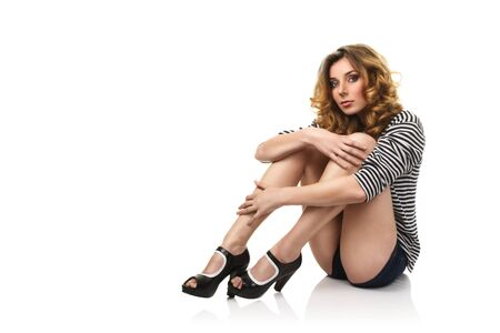 Sexy young girl with long legs sitting on floor isolated over white background photo