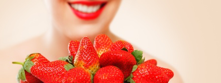 ripeness: Young woman eating red ripe strawberry close-up studio shot Stock Photo