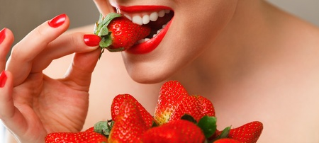 Young woman eating red ripe strawberry close-up studio shot photo