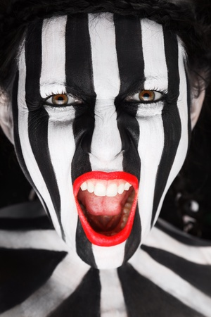 Young woman soccer fan with stripped face paint aggressive screaming