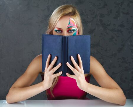 Young blonde woman reading book in dark room photo