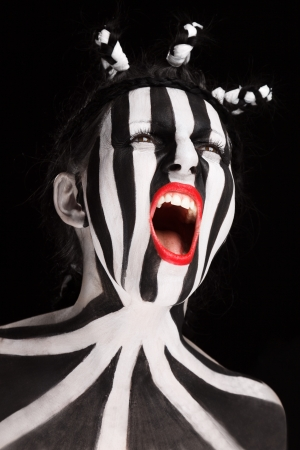 stripped: Young woman soccer fan with stripped face paint aggressive screaming