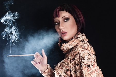 Young woman smoking slim cigarette against dark background photo
