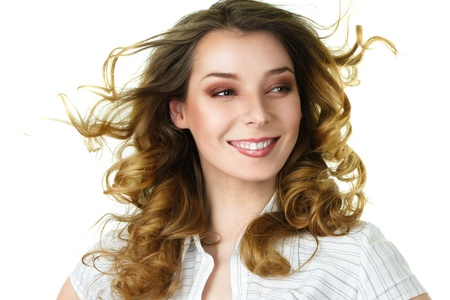 sidewards: Attractive smiling woman with long curly hair flowing under wind isolated over white background