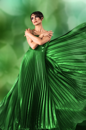 sidewards: Sexy young girl in long flowing dress against green nature background