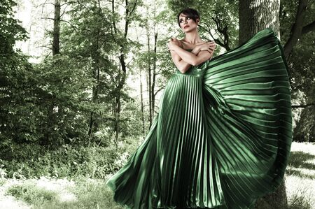 sexy fairy: Young attractive woman in green long dress at forest