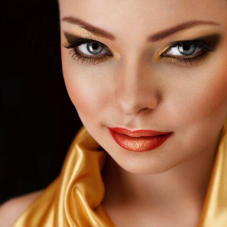 labios sexy: Modelo de manera atractiva con el oro y creativa de maquillaje en la cara