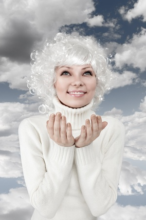 Emotional young blonde woman in white sweater with open hands looking up photo