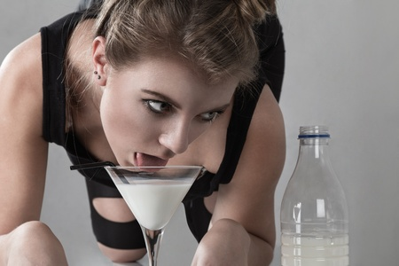 cosplay: Young cat woman drink milk from glass looking to bottle Stock Photo