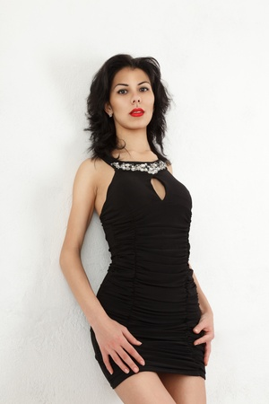 Young woman in small black mini dress near wall photo