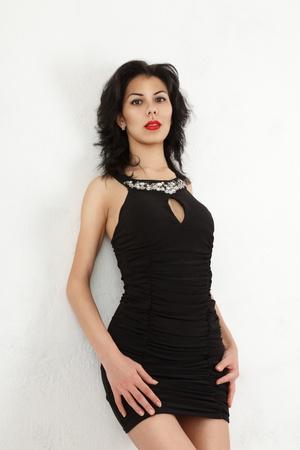 Young woman in small black mini dress near wall