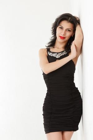 Young woman in small black mini dress near wall Stock Photo - 12774425