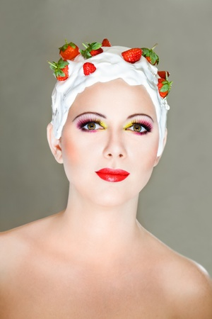 Young woman with hairstyle made from milk and red ripe strawberry photo
