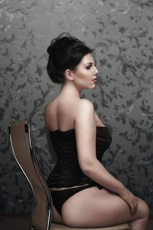 Attractive young woman in black lingerie sitting on chair photo