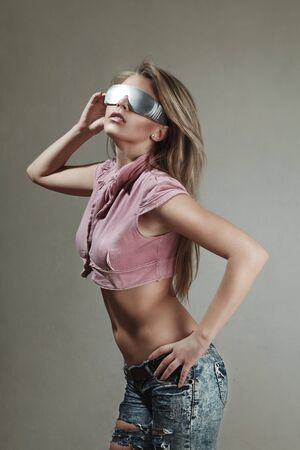 Young blonde woman looking through futuristic glasses photo
