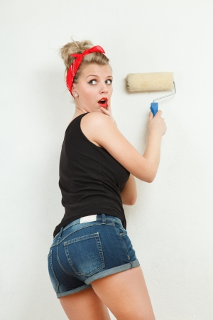 Young classic pin-up woman painting wall with paint roller photo