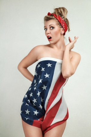 Sexy blond pin-up model wrapped in american flag