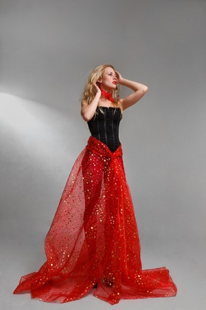 sidewards: Young sexy blonde girl with long gorgeous red dress Stock Photo