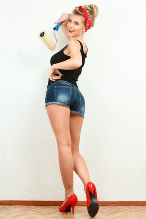 painter and decorator: Young classic pin-up woman painting wall with paint roller Stock Photo
