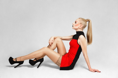 Young blonde fashion model sitting on floor posing for lookbook portfolio Stock Photo