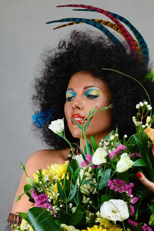 african fashion: Fashion model made make-up african style with bouquet flowers