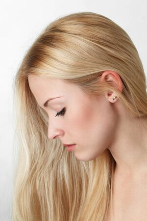 woman looking down: Young blonde woman with long hair looking down Stock Photo