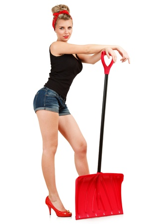 Classic sexy pin-up girl in shorts with red snow shovel