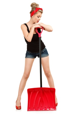 Classic sexy pin-up girl in shorts with red snow shovel photo