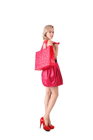 looking over shoulder: Young blonde woman in pink mini dress with shopping bag isolated over white