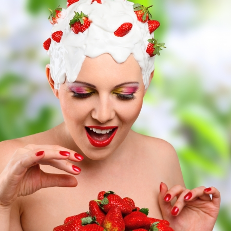 Happy woman with hairstyle made from milk and red ripe strawberry photo