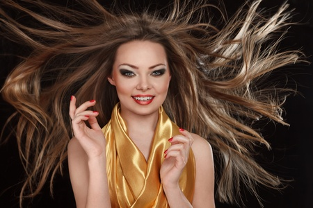 strong wind: Young smiling woman with long hair fluttering under wind