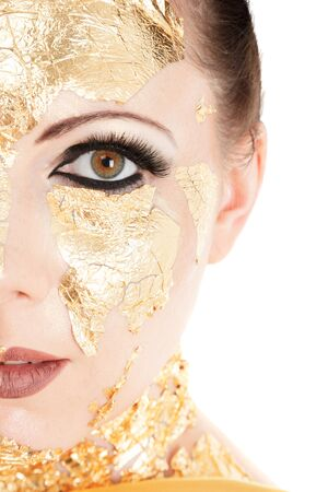 Young woman face with gold make-up mask isolated on white background photo