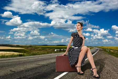 sidewards: Young woman sitting on suitcase on country road