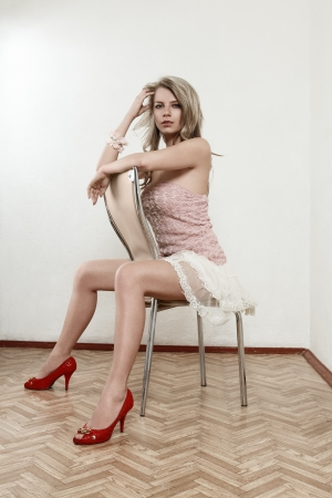 Sexy young blonde girl in mini dress sitting on chair inside empty room photo