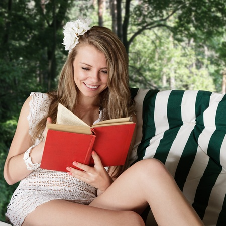 Young blonde woman reading a book resting in lounge photo