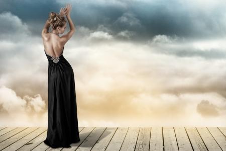 skinny: Mujer joven rubia en el abierto de nuevo elegante vestido negro Foto de archivo