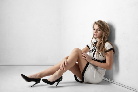 high heels woman: Sexy young woman with long legs sitting on floor near room wall Stock Photo