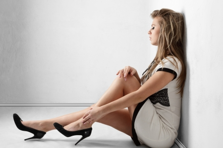 woman sitting floor: Sexy young woman with long legs sitting on floor near room wall Stock Photo