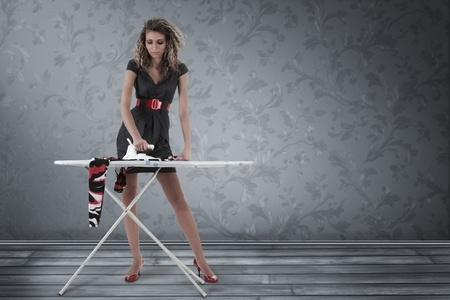 Beautiful woman ironing clothing in empty room photo