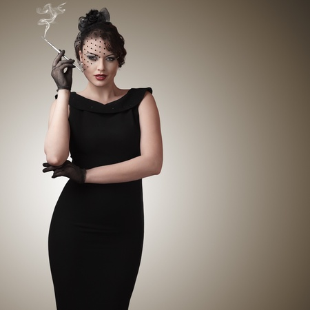 Attractive young woman with slim cigarette retro style portrait Imagens