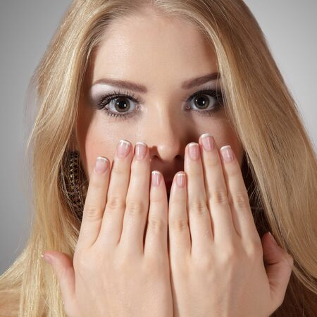 Pretty surprised woman with hands over mouth photo