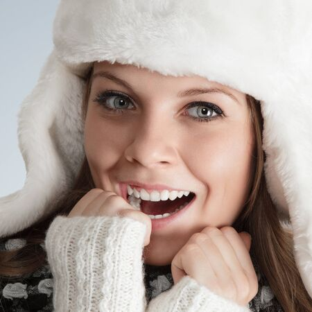 Beautiful young woman in white hat ear flaps photo