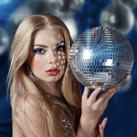 Beautiful young woman holding disco ball at night club photo