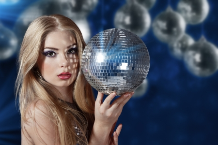 Beautiful young woman holding disco ball at night club
