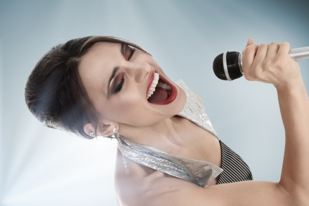 Attractive young female jazz singer singing with microphone photo
