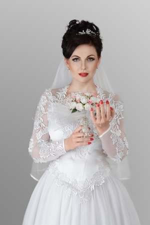 Happy young bride with wedding bouquet photo