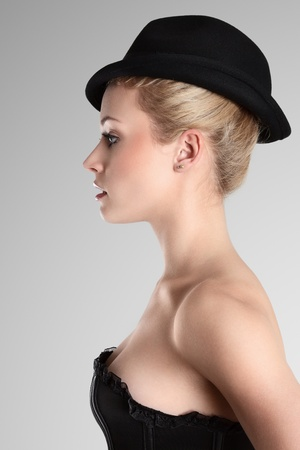 Blonde fashion model in hat looking away. Side view photo
